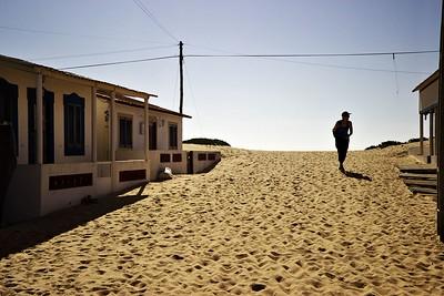 Tam, kde se na Ilha de Faro nachází silnice, tam je poměrně hustá zástavba. V místech, kde silnice končí, se postupně její hustota zmenšuje a stavby získávají na improvizovanosti. Tohle je víceméně přímo u konce silnice. Za horizontem se ostrov zase svažuje směrem k moři - má na šířku jen pár stovek metrů.