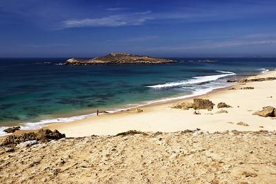 Druhá zdejší pláž s výhledem na ostrov s rozvalinami římského opevnění. Vzadu na obzoru je vidět přístav v Sines.