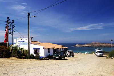 """Už na cestě do Algarve. Míjeli jsme velký přístav v Sines a hledali jsme nějaké místo, odkud bychom si ho mohli vyfotit. Nakonec jsme se vydali po náhodné odbočce směrem na pobřeží. Jeli jsme po ní několik kilometrů pro rozbité staré cestě a domnívali se, že cesta co nevidět skončí...a dojeli jsme na velké parkoviště s restaurací u staré pevnosti a s výhledem na rozvaliny ještě mnohem starší pevnosti na nedalekém ostrůvku. Aneb, jak tady prohlásila Trofo: """"Na Portugalsku je úžasné, že někam úplně náhodně odbočíte, chvíli jedete a když dojedete na konec, tak je to tam hezký."""""""