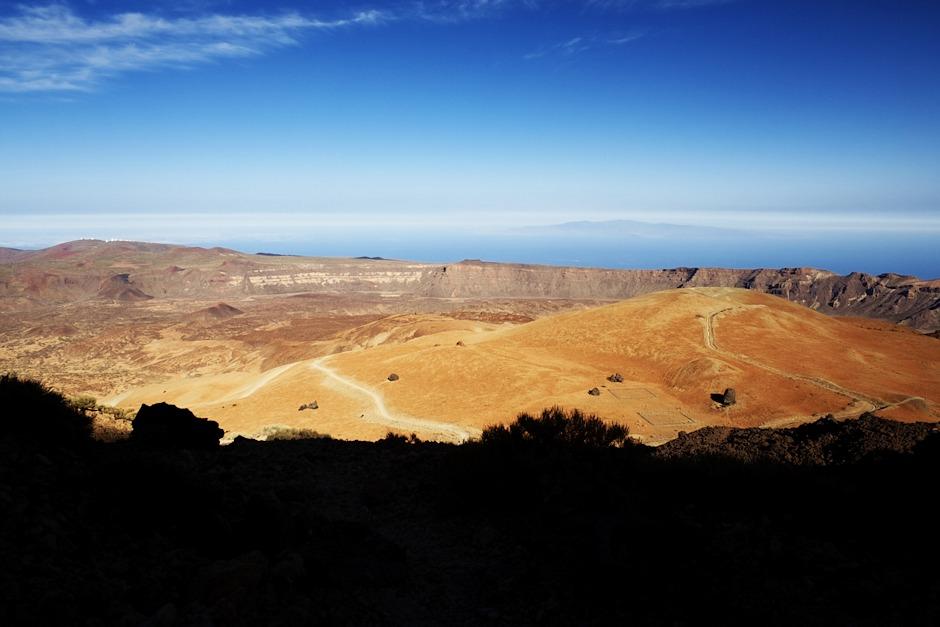 Montaňa Blanca, za ní kaldera (vlevo je stále vidět observatoř Izaňa) a v dálce ostrov Gran Canaria. Jsme zhruba v 2900 metrech.
