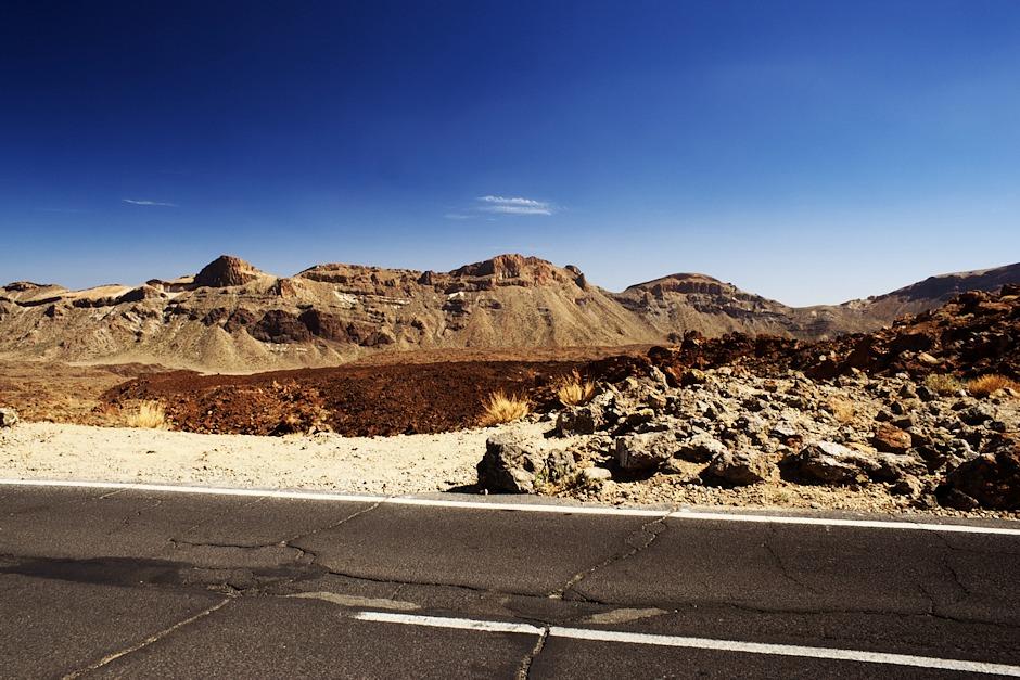Lávová pole a v dálce okraj kaldery Caňadas, tvořený vysokými útesy.