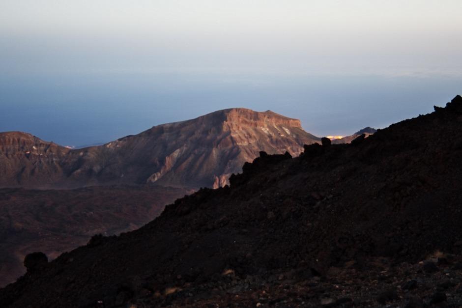 Za lávovým proudem a kalderou prosvítají světla měst na jižním pobřeží. Opět - je větší tma, než se z fotografie zdá.