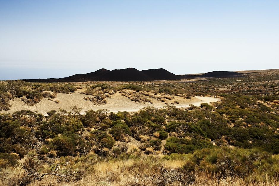 V dálce vidíme náš cíl, sopku Volcán de Fasnia. Vypadá hrozně zvláštně - působí dojmem, že uprostřed prosluněné krajiny stojí několik kopců, na které cosi vrhá stín. Ve skutečnosti jsou ale skutečně tak černé.