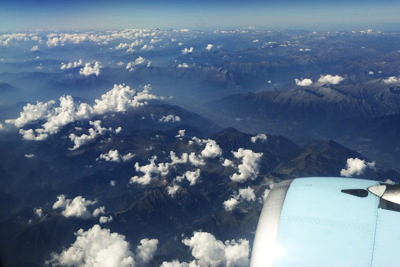 Itálie, východní cíp jezera Como (v operu v údolí vlevo uprostřed), zhruba uprostřed fotografie se pod oparem nachází město Morbegno. V pozadí vlevo lezou z mraků špičky Walliských Alp.