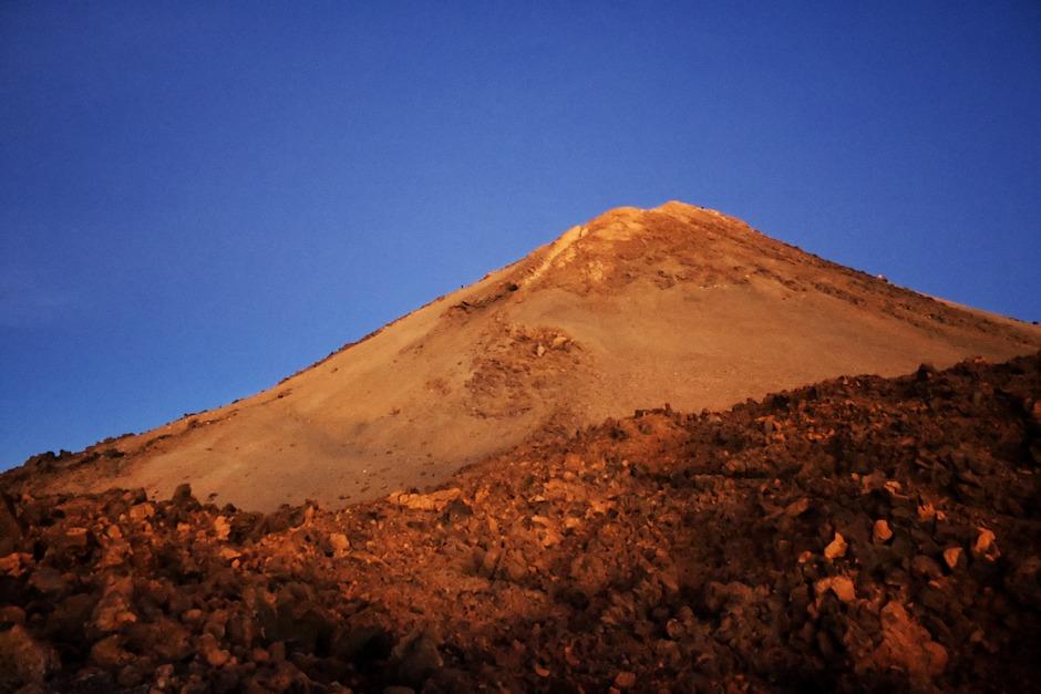Na sebou vidíme hlavní vrcholek Teide. Je nějak vyšší, než by se nám zamlouvalo. Na vrcholku vidíme poblikávání čelovek. Jeden člověk je dokonce na vrcholku vidět i na téhle fotce. Další stoupají po úbočí vlevo. Je bizarní, jak relativně mírný se sklon úbočí takhle z dálky a na fotografii zdá oproti tomu, když se po něm skutečně šplháte.