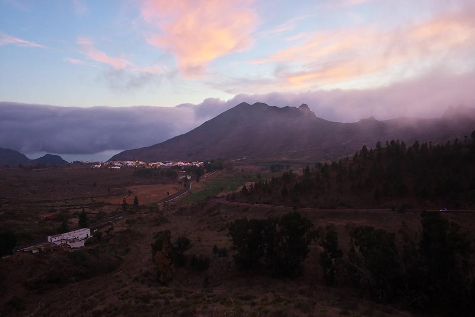 Pohled na Santiago del Teide. Hřeben uprostřed a vpravo je ten, který Santiago dělí od vesnice Masca a na kterém jsme už byli. To, co v průhledu vlevo od Santiaga vypadá jako voda, je ve skutečnosti jen obloha pod oblačným příkrovem, moře je ještě o slušný kus níž.