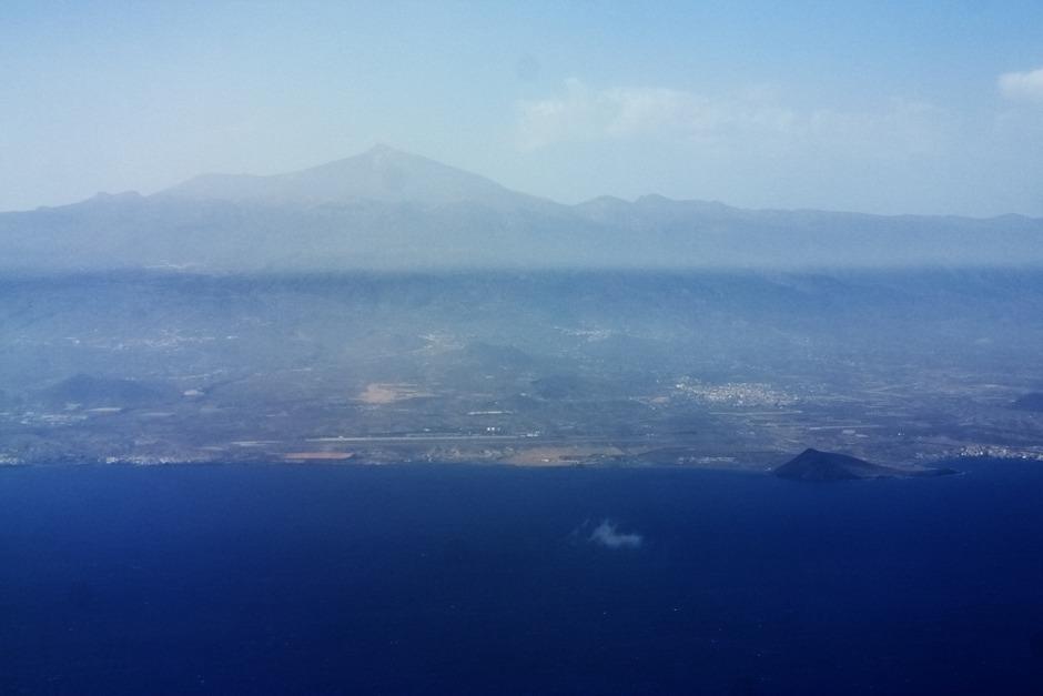 """Teide už zřetelnější. Dole uprostřed letiště Tenerife Sur, na kterém budeme přistávat. Vpravo dole je hora Montaňa Roja, Červená hora, která se nachází nedaleko letiště a údajně se jí také říká """"malý Gibraltar"""", vzhledem k podobnému tvaru (byť tím podobnosti končí)."""