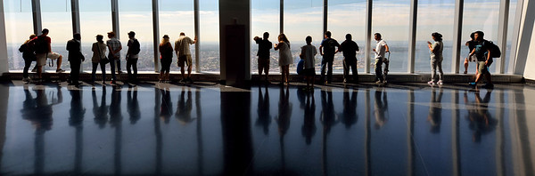 A wide view of people, and their reflections  at the window of the observation deck.