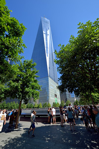 People stroll along the plaza between the north and south Reflection Pool Memorials.