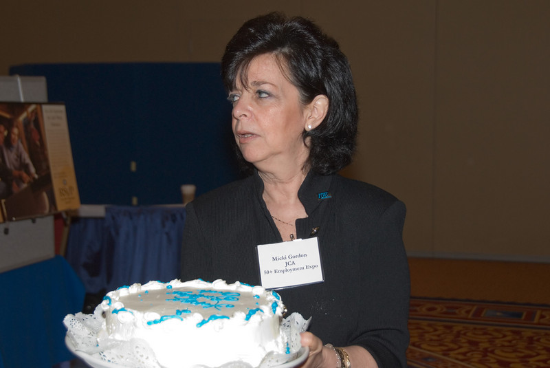 50+ Employment Expo -- Micki Gordon with Birthday cake for Arch Campbell