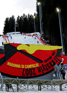 Workers put some final touches on a finish area sign as moguls training goes on in the background at the FIS Freestyle World Ski Championships at Madonna di Campiglio, Italy, Thursday, March 8, 2007.   Photo by Mike Ridewood
