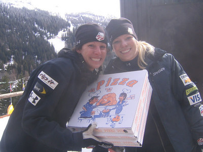 Aerial skiers Emily Cook (left) and Lacy Schnoor double as pizza delivery girls for their coaches in between women's and men's training sessions Thursday at Madonna di Campiglio (credit: Doug Haney/U.S. Ski Team)