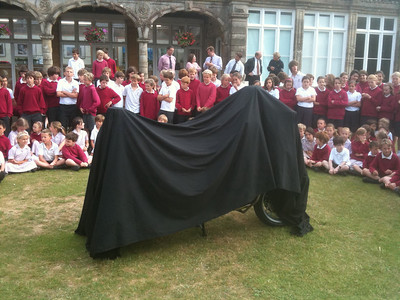 Pupils await the unveiling of the mystery object underneath the black covers.