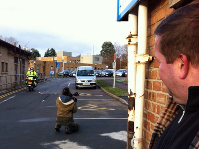 Jemma films Mel riding away from the pathology labs at Frenchay Hospital, while Mel's husband Martyn looks on