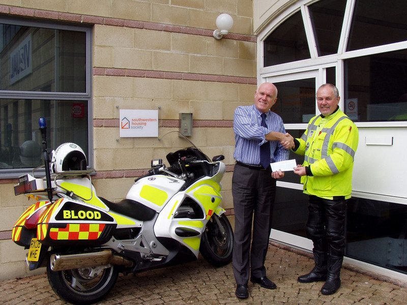 Phil Yorke, Chief Executive of Southwest Housing Society, presents a cheque to Freewheelers volunteer Doug Harding.