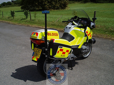 "Rear-right view showing the blue light pole and panniers. At the bottom of the pole, just to the right of the word ""BLOOD"" and above the indicator you might be able to see the clear lenses that cover the flashing red and blue LED lights."