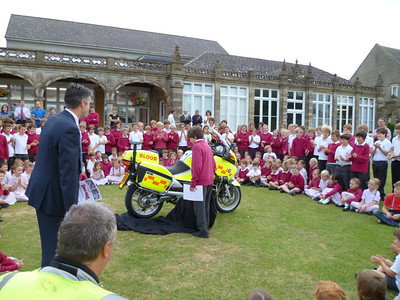 Headmaster Ian Murphy looks on as the name-the-bike competition winner unveils the bike