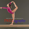Attractive young female gymnast performs on the balance beam