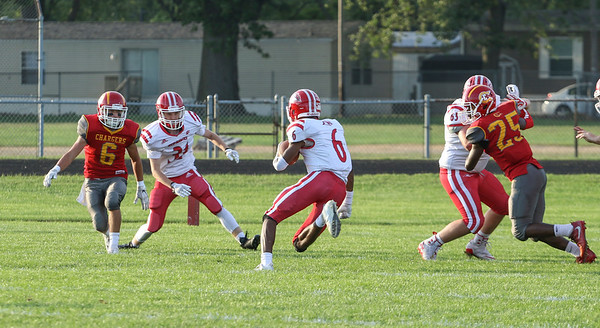 Branden Beachy | The Goshen News<br /> Goshen senior Daveyon Sandford runs through the gap to score the first touchdown of the game in Elkhart Friday night.