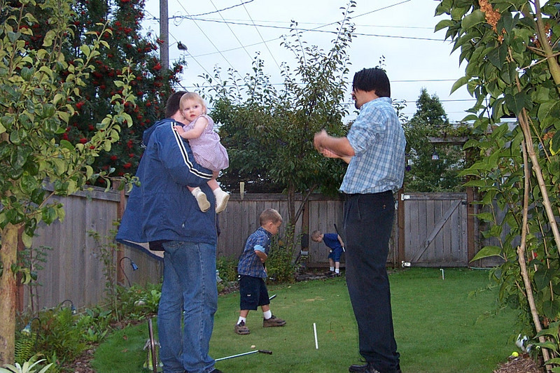 Jeff (at left, holding his daughter Samantha) talks to Jaime on Kirk's putting green.<br /> [Kirk & Mary Lou's farewell party and garage sale - August 2003]