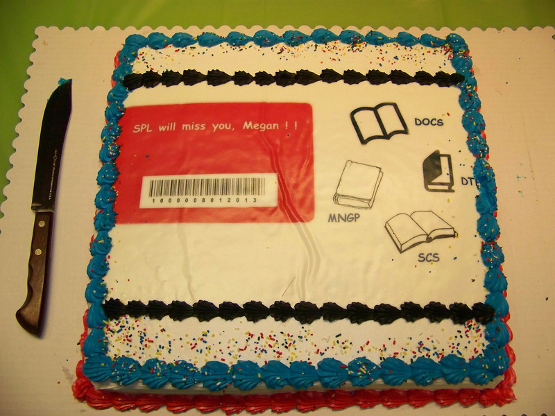 Megan's cake was decorated with a Q-Card (for Borrower Services) and a book icon for each of the other departments she worked in during her SPL career.<br /> [Megan's retirement party - August 1, 2013]
