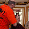 Donna looks on skeptically as Dad attempts to style Mom's hair.