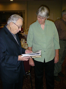 Ingrid Wicken showing her new History of Skiing in So. Calif. book to Glen, who is prominently featured.