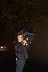 Ed Gray, Car 1, does what is necessary to keep equipment dry at a job in the rain in Hackensack.