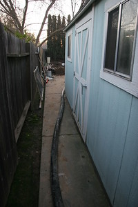 Concrete hose winds around the side of the house