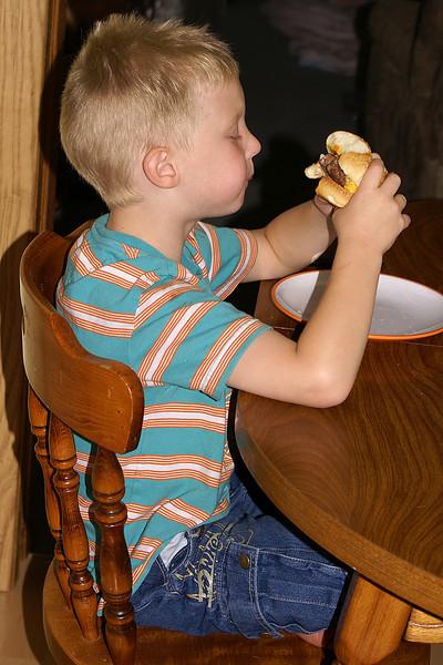 John enjoying a burger at dinner time.