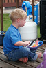 Sitting on the deck playing with a toy keyboard.<br /> <br /> I snuck outside and poked my head around the corner to capture this shot of John. I didn't want him to know I was there as he would have made a funny face.