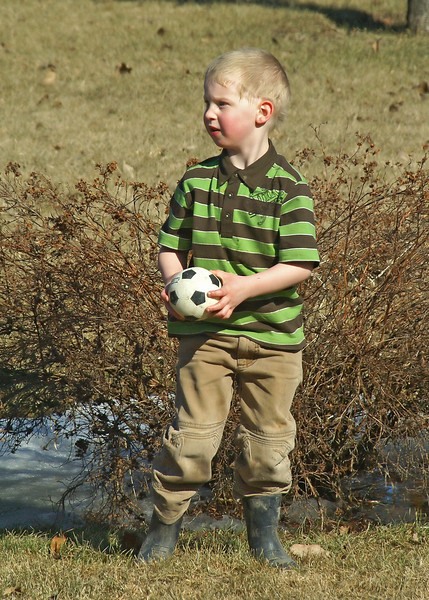 John playing in the backyard with a soccer ball he noticed in the shed.