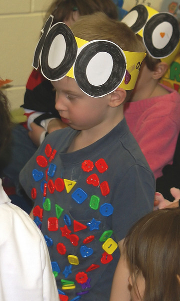 Part of the 100 Days activities, the children had to wear a shirt with 100 on it. John is wearing a shirt with 100 buttons on it.