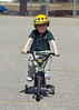 Hard to see with the smaller image, but he has a look of determination on his face.<br /> <br /> Riding his new two wheeler in the basketball court at the school Wendy works at.