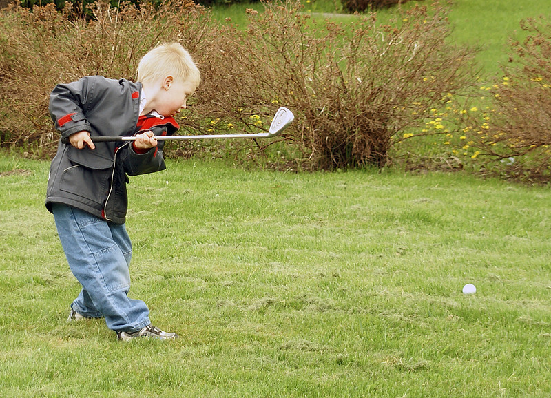 Practicing his golf swing in the back yard.