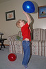John playing with some balloons in the living room.