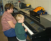 Playing with the piano at the school. John loves musical instruments.