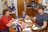 John and Mom builds a gingerbread house while Grandma looks on.