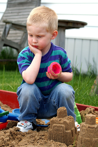 While building his sand castle, he stops to think - I wonder what he is thinking about?