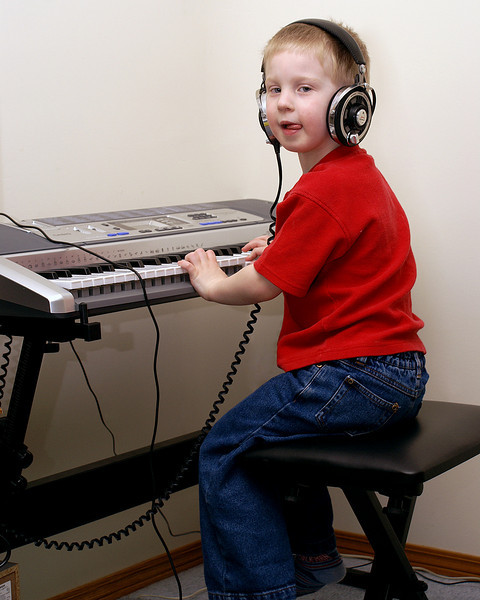Grandma got a stand and stool for the keyboard. Here John is trying it out for size.