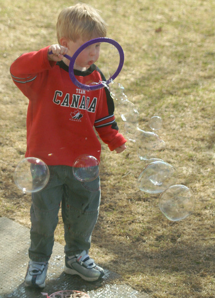 Blowing bubbles in the front yard. This was taken without his knowledge thru the living room window.