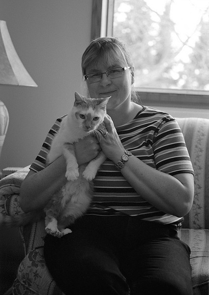 Wendy in the living room holding Spike who *really* hates being held.<br /> <br /> Photo taken with a Leica R4 with a Leitz 35-70mm lens. Film was bulk loaded Kodak T-max 100 developed in D76 for 7.25 mins at 18C. Light provided by living room window.