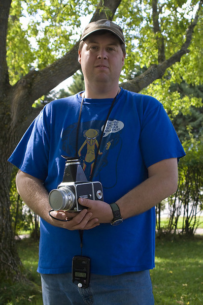 Photo of me taken by John with my Sony A100. I'm holding a Hasselblad 500 C/M, and that item hanging below the camera is my hand held light meter. Apparently the Sony A100 and the light meter agree - the light meter is indicating 1/250th at F6.3 which is also what the Sony A100 used to shoot this image. This photo was taken in our front yard. It isn't the sharpest but you can still tell who it is.