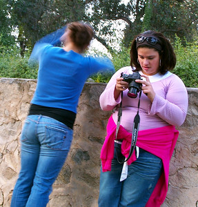 Yarissa on the phone and Evynne playing with her camera.