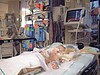 This would be a typical scene for a parent when coming in to see your child for the first time. The 'TV' screen shows his vital signs. The machines with the red tags are IV pumps, pushing drugs (pain killers or what ever the child needs), into his vein(s). You can also see the restraints on his wrists. These are to keep him from ripping out all his lines, and tubes.
