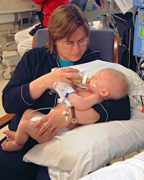 Mom holding John as she feeds him a bottle. The intensivist didn't think John would even take a bottle and wanted to feed him via tube into his stumache, but Wendy argued with the Doctor until he gave in - she would at least try to bottle feed him first. And sure enough, he took a 5 oz feed the first attempt. A total of 12 oz for the day. Proving that even tho a Doctor wears a white coat, it don't make him smarter than anyone else! He later appogized to Wendy - as she was right. He was wrong.
