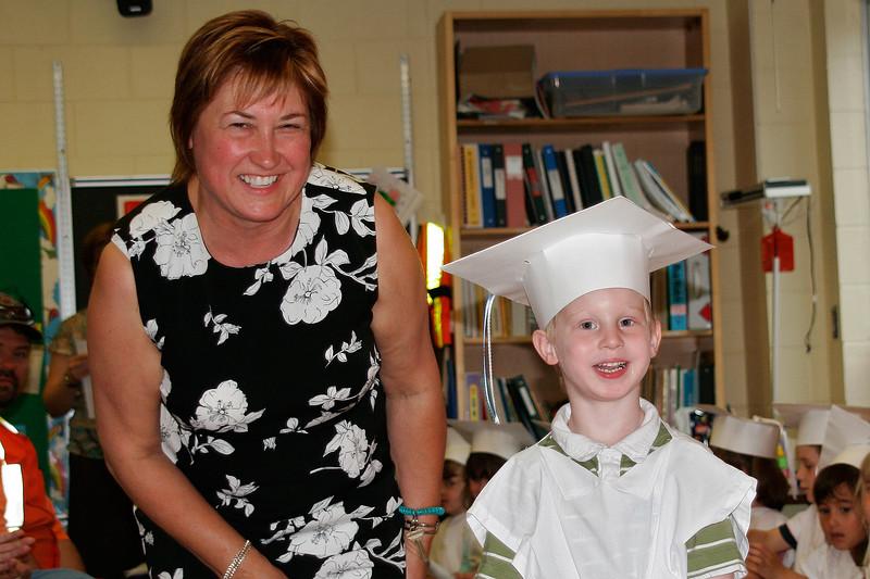Mrs. Querel (the schools Principal) congratulates John and passes him his scroll.