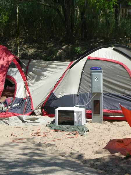 Weirdest campsite ever.<br /> <br /> No people around. Collapsed middle tent (weather was fine) with open door (and sand all over the place). Microwave and alarm clock plugged into power outlet.