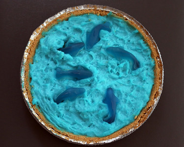 Shark Week Oreo Truffle Pudding Pie: White chocolate pudding (with blue food dye) on top of a layer of Golden Oreo truffle (Oreos mixed with cream cheese), over a graham cracker crust.  Topped with gummy sharks.  So delicious.