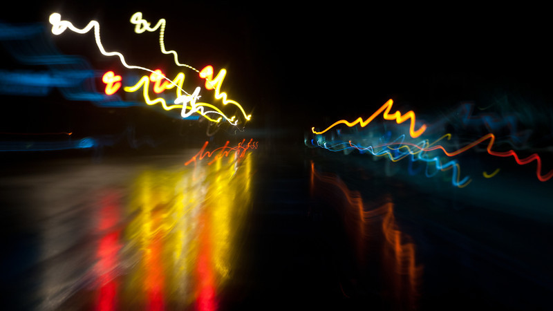 Zoom<br /> <br /> This is shot taken from the car just outside our neighborhood.  During the 1 second exposure, the lens is zoomed from 24m to 70mm.  The red and yellow pattern to the left is actually a traffic signal changing color.  The street is wet from rain.